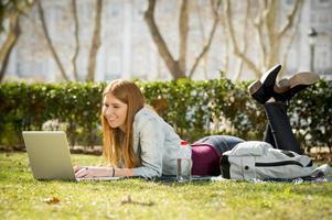 Studentenmädchen, das auf Campus-Parkgras mit Computerstudien liegt foto