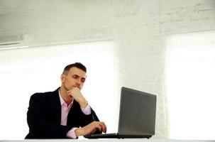 Geschäftsmann, der an einem Laptop arbeitet foto