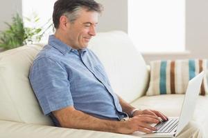 lächelnder Mann, der auf einem Sofa mit Laptop sitzt foto
