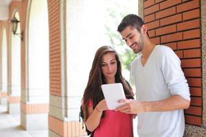 glückliche Studenten, die Computer benutzen foto