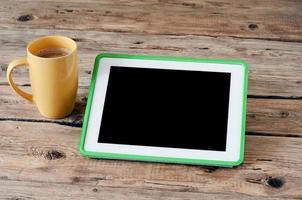 Tablet-Computer mit Kaffeetasse foto
