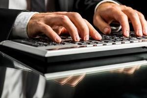 Geschäftsmann, der am Computer durch Schreibmaschine arbeitet foto