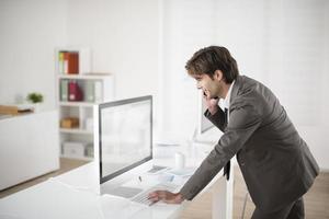 Geschäftsmann-Telefone lehnen sich an seinen Computer foto