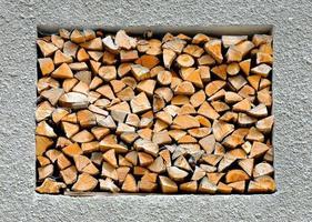 abstrakter Hintergrund mit gestapeltem Brennholz in der Wand