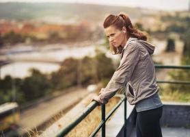 Fitness junge Frau, die in die Ferne im Freien schaut foto