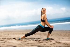 Schönheit am Strand macht Übungen foto
