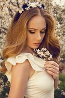 schönes Mädchen mit den roten Haaren, die am Frühlingsgarten aufwerfen
