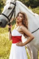 schöne sinnliche Frauen mit weißem Pferd foto