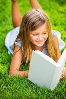 süßes kleines Mädchen, das Buch draußen auf Gras liest foto