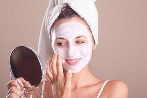 Mädchen, das Maske auf Gesicht anwendet und in den Spiegel schaut foto