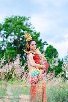 Frau, die typisches thailändisches Kleid mit thailändischem Stil trägt foto