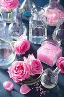 Alchemie und Aromatherapie mit Rosenblüten und chemischen Flaschen