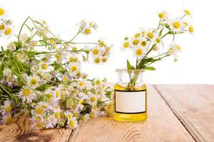 Alternativmedizin-Konzept - Flasche mit Kamille auf Holz ta foto