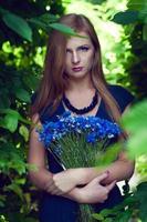schöne Blondine posiert mit einem Kornblumenstrauß