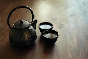 Bild der traditionellen östlichen Teekanne und der Teetassen auf Holzschreibtisch