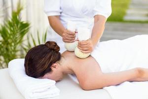 Brünette mit Massage mit Kräuterkompressen