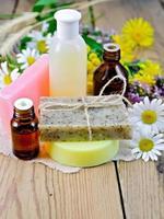 Öl mit Lotion und Seife mit Wildblumen auf dem Brett foto