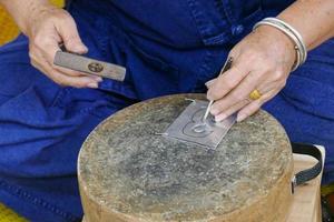 Handwerker schnitzt Silberplatte Kunst foto