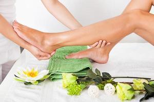 Frauenfüße, die sich einer Massage unterziehen foto