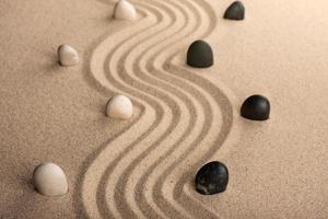 Linie schwarze und weiße Steine, die auf dem Sand stehen