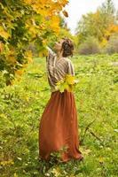 junge schöne Frau, die Herbstahornblätter sammelt foto