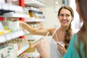 Mädchen wählt Parfüm im Laden foto
