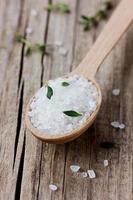 Meersalz im Löffel mit einem frischen Kräuterthymian foto