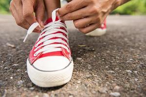 Frau schnürt ihre Schuhe, bevor sie im Park joggt foto