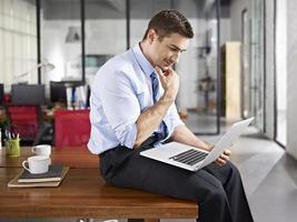 kaukasischer Geschäftsmann, der im Büro arbeitet foto
