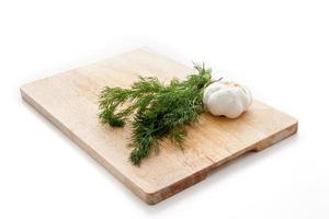 Dill und Knoblauch auf einem Holzbrett foto