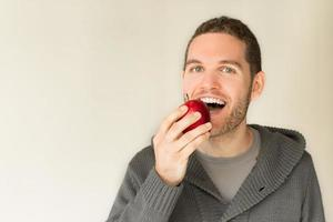 junger kaukasischer Mann, der einen Apfel isst foto