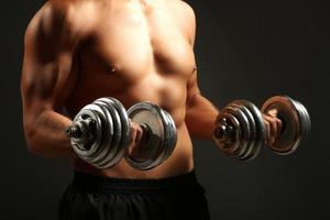 schöner junger muskulöser Sportler mit Hanteln auf dunklem Hintergrund