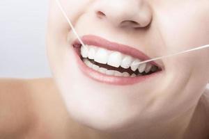 Mund-Nahaufnahme der kaukasischen Frau mit Zahnseide. foto