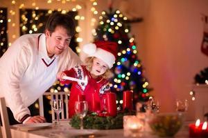 Vater und Tochter zünden Weihnachtskerzen an