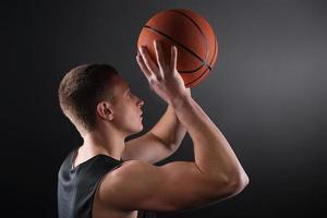 kaukasischer männlicher Basketballspieler, der den Ball frei wirft foto