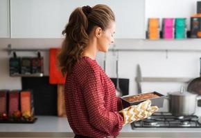 Frau, die in der Küche steht und heiße Laibdose hält
