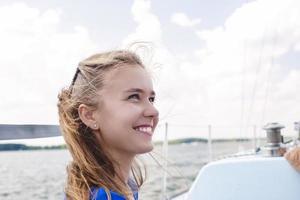 Porträt der glücklichen kaukasischen Frau, die auf Yacht segelt foto