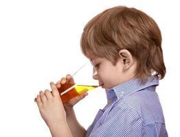 süßer kaukasischer Junge, der ein Glas Apfelsaft trinkt foto