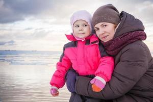 Outdoor-Porträt der kaukasischen Familie an der Winterseeküste, junge Mot foto