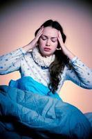 asiatische kaukasische Frau, die Kopfschmerzen hat, die auf Bett sitzen