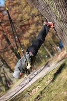 Outdoor-Suspensionstraining im Wald - kaukasischer Mann am Baum