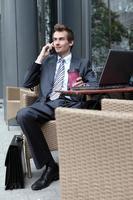 junger kaukasischer Geschäftsmann, der seinen Laptop im Kaffeetrinken benutzt foto