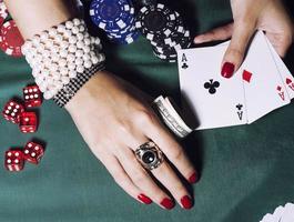 Hände der jungen kaukasischen Frau mit roter Maniküre im Kasino