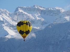 schwarzer und gelber Ballon mit dem schneebedeckten Berg