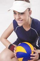 Porträt der lächelnden kaukasischen professionellen weiblichen Volleyballspielerin im Volleyball-Outfit foto