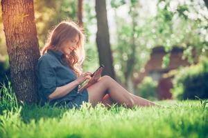 hübsche junge kaukasische Frau, die draußen unter einem Baum sitzt und spricht foto