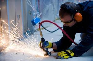 Funken fliegen, während Arbeiter Bolzen schneiden foto