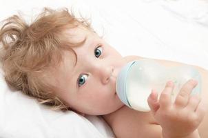kleines Baby mit lockigem Kopf saugt eine Flasche Milch foto