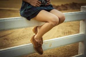 Frauen mit braunem Schuh auf dem weißen Zaun foto