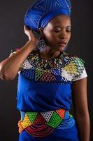 afrikanisches weibliches Modemodell, das auf Schwarz aufwirft foto